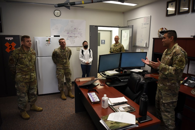 A group of military members surround one speaking behind a desk.