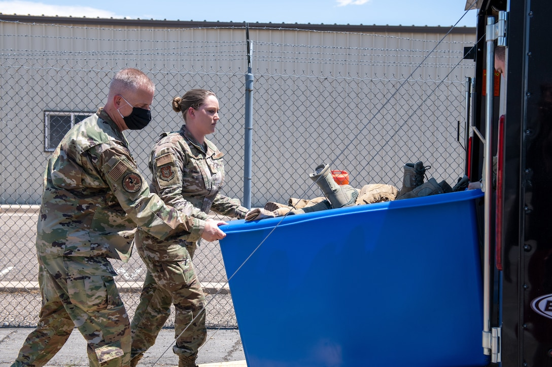 Col. Brett Newman, 419th Maintenance Group commander, helps Staff Sgt. Jayci Winter from the 419th MXG push a cart of collected boots into a trailer for a boot drive at Hill Air Force Base, Utah, on July 7, 2021.