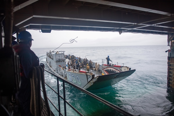 210630-N-IJ902-1139 Philippine Sea (June 30, 2021)—Sailors throw mooring lines to Landing Craft Utility 1633 (LCU 1633),  as it enters the well deck of amphibious dock landing ship, USS Germantown (LSD-42). Germantown, part of Amphibious Squadron 11, along with the 31st Marine Expeditionary Unit, is operating in the U.S. 7th Fleet area of responsibility to enhance interoperability with allies and partners and serve as a ready response force to defend peace and stability in the Indo-Pacific region. (U.S. Navy photo by Mass Communication Specialist Seaman Apprentice Nicholas M. Skyles)