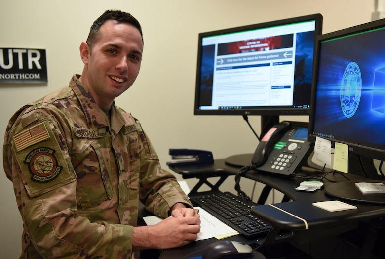 Airman stands next to computer and smiles at camera.