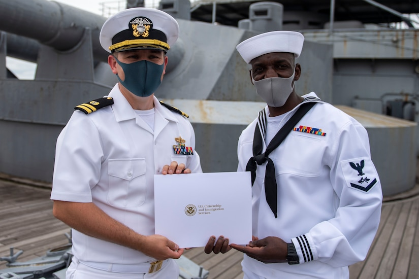 Two male sailors display a certificate.