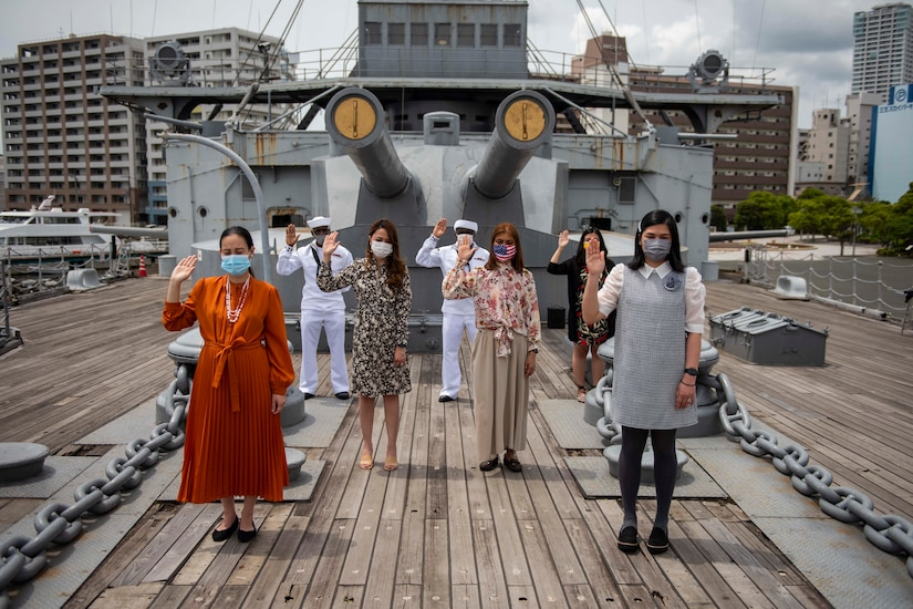 Seven men and women hold up their right hands outdoors on a ship.