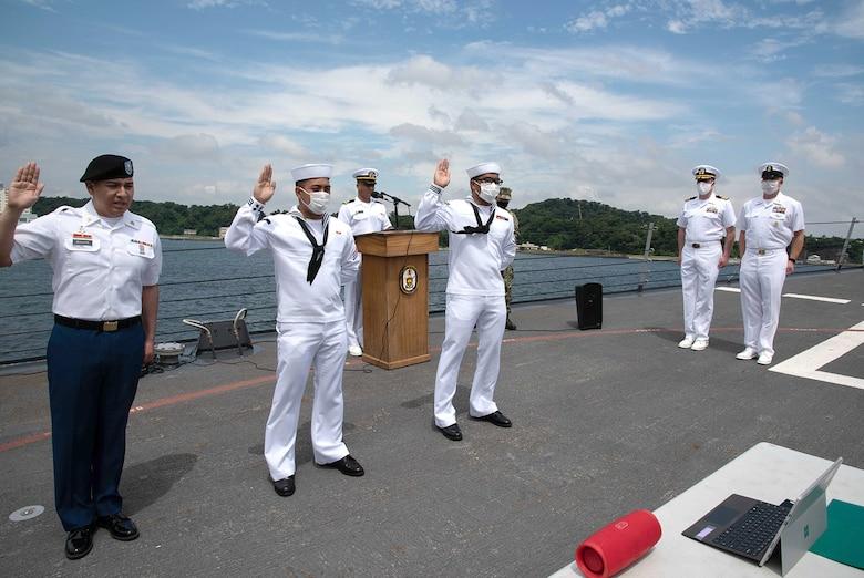 Sailors participate in a naturalization ceremony.
