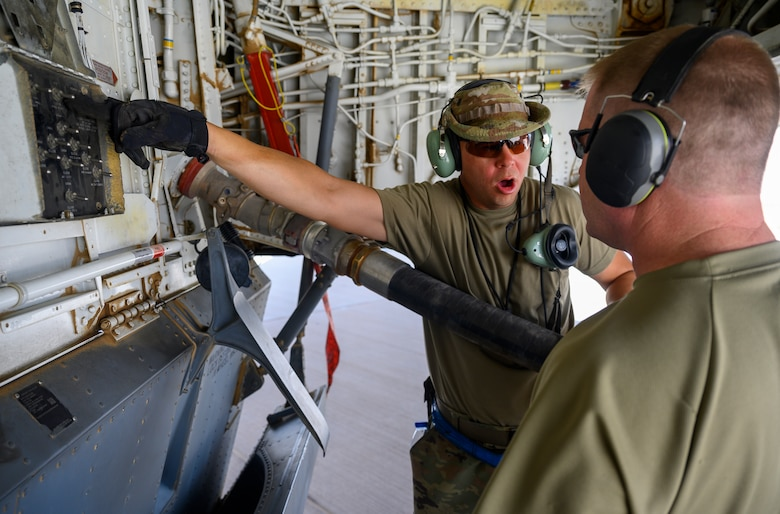 U.S. Air Force Tech. Sgt. Adam Barrett, 157th Expeditionary Fighter Generation Squadron dedicated crew chief, explains part of the hot pit refueling process on a U.S. Air Force KC-135 Stratotanker, Prince Sultan Air Base, June 25, 2021. This event demonstrated the success of several weeks of hot-pit refueling cross-airframe training between 378th and 379th Air Expeditionary Wing maintainers, expanding both wings ability to provide agile support for theater operations. (U.S. Air Force photo by Senior Airman Samuel Earick)