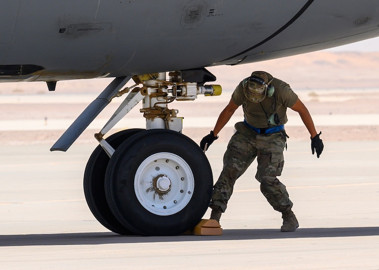 U.S. Air Force Tech. Sgt. Adam Barrett, 157th Expeditionary Fighter Generation Squadron F-16 dedicated crew chief, places chalks on a U.S. Air Force KC-135 Stratotanker for a hot-pit refueling, Prince Sultan Air Base, June 25, 2021. This event demonstrated the success of several weeks of hot-pit refueling cross-airframe training between 378th and 379th Air Expeditionary Wing maintainers, expanding both Wings ability to provide agile support for theater operations. (U.S. Air Force photo by Senior Airman Samuel Earick)