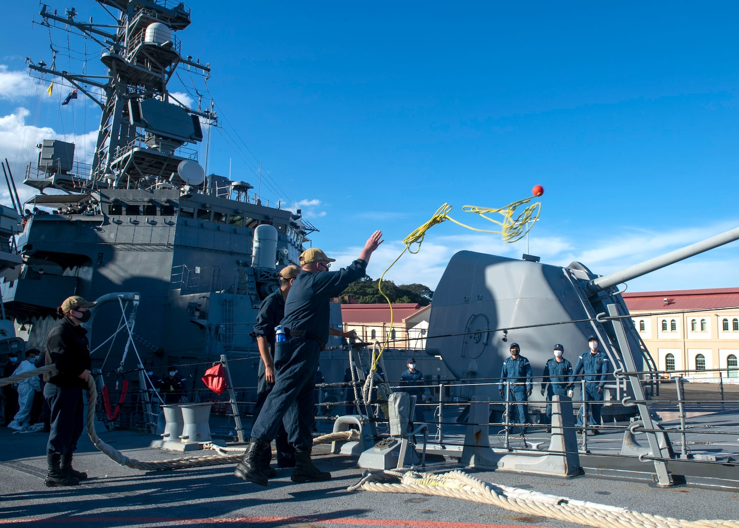 210703-N-HG846-1217 SYDNEY (July 3, 2021) – Sailors aboard Arleigh Burke-class guided-missile destroyer USS Rafael Peralta (DDG 115) throw a messenger line to sailors aboard the Japan Maritime Self Defense Force Takanami-class destroyer JS Makinami (DD 112) as they moor alongside in support of Pacific Vanguard 2021. Pacific Vanguard, an exercise involving U.S., Australian, Republic of Korea navies and Japan Maritime Self Defense Force, is designed to strengthen maritime operations in the multilateral environment. (U.S. Navy photo by Mass Communication Specialist 3rd Class Daniel Serianni)