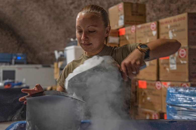 Staff Sgt. Rachel Rhoads, 379th Expeditionary Medical Support Squadron blood transshipment center NCO in charge, scoops dry ice into a bucket July 1, 2021, at Al Udeid Air Base, Qatar.