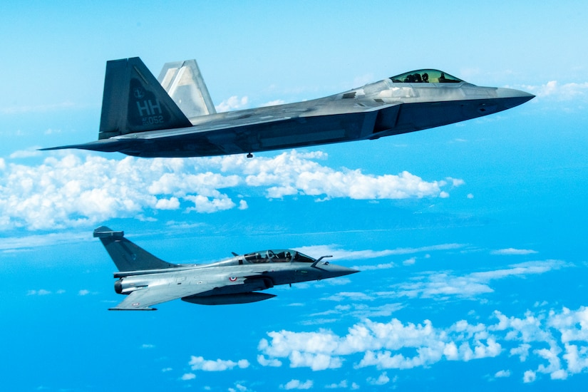 Two fighter jets fly in formation.