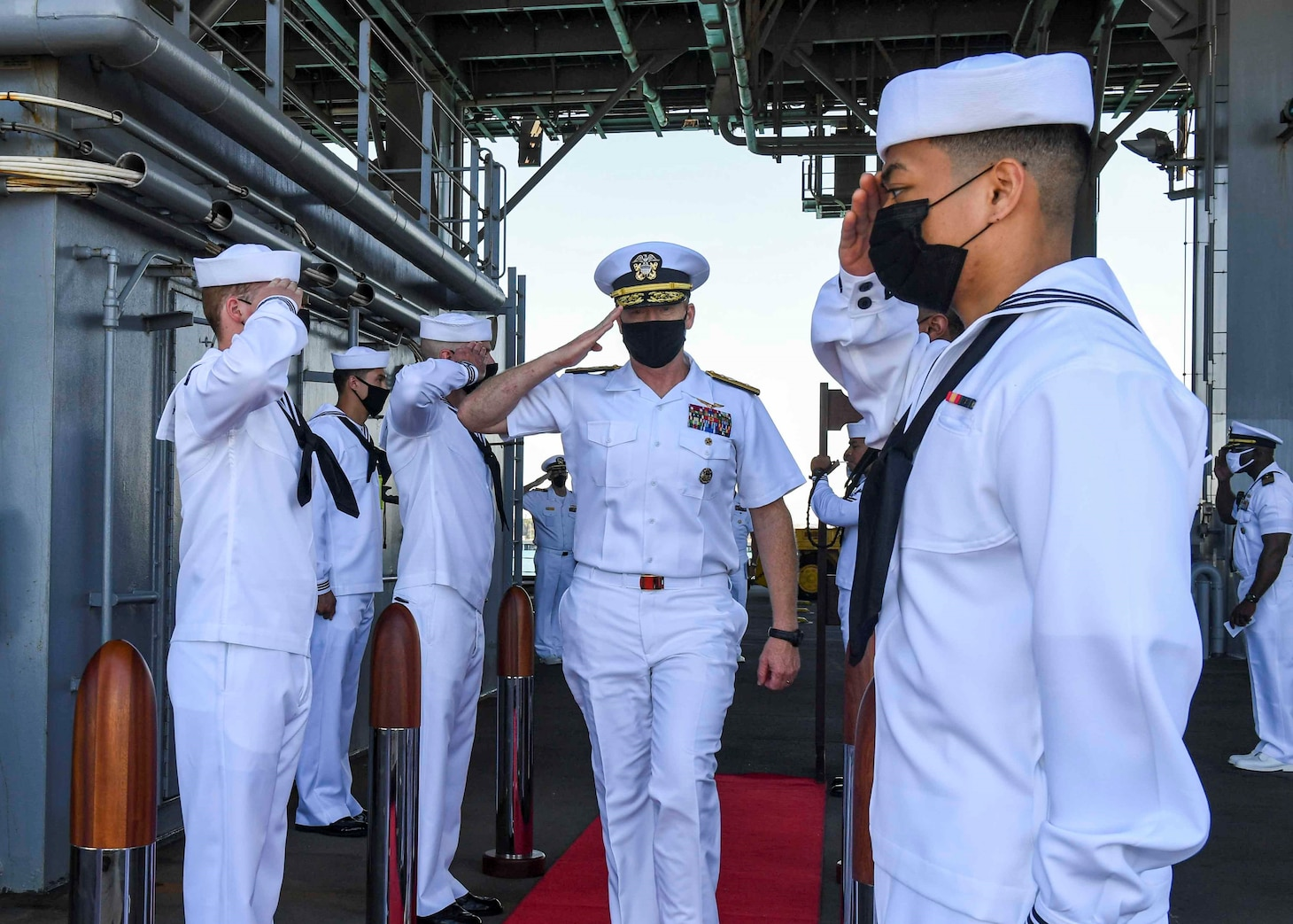 """(July 8, 2021) Rear Admiral Ben Reynolds, Director of Maritime Headquarters, U.S. Naval Forces 6th Fleet, walks through the side boys after receiving a tour aboard the Expeditionary Sea Base USS Hershel """"Woody"""" Williams (ESB 4) in the Atlantic Ocean, July 8, 2021. Hershel """"Woody"""" Williams is on a scheduled deployment in the U.S. Sixth Fleet area of operations in support of U.S. national interests and security in Europe and Africa."""