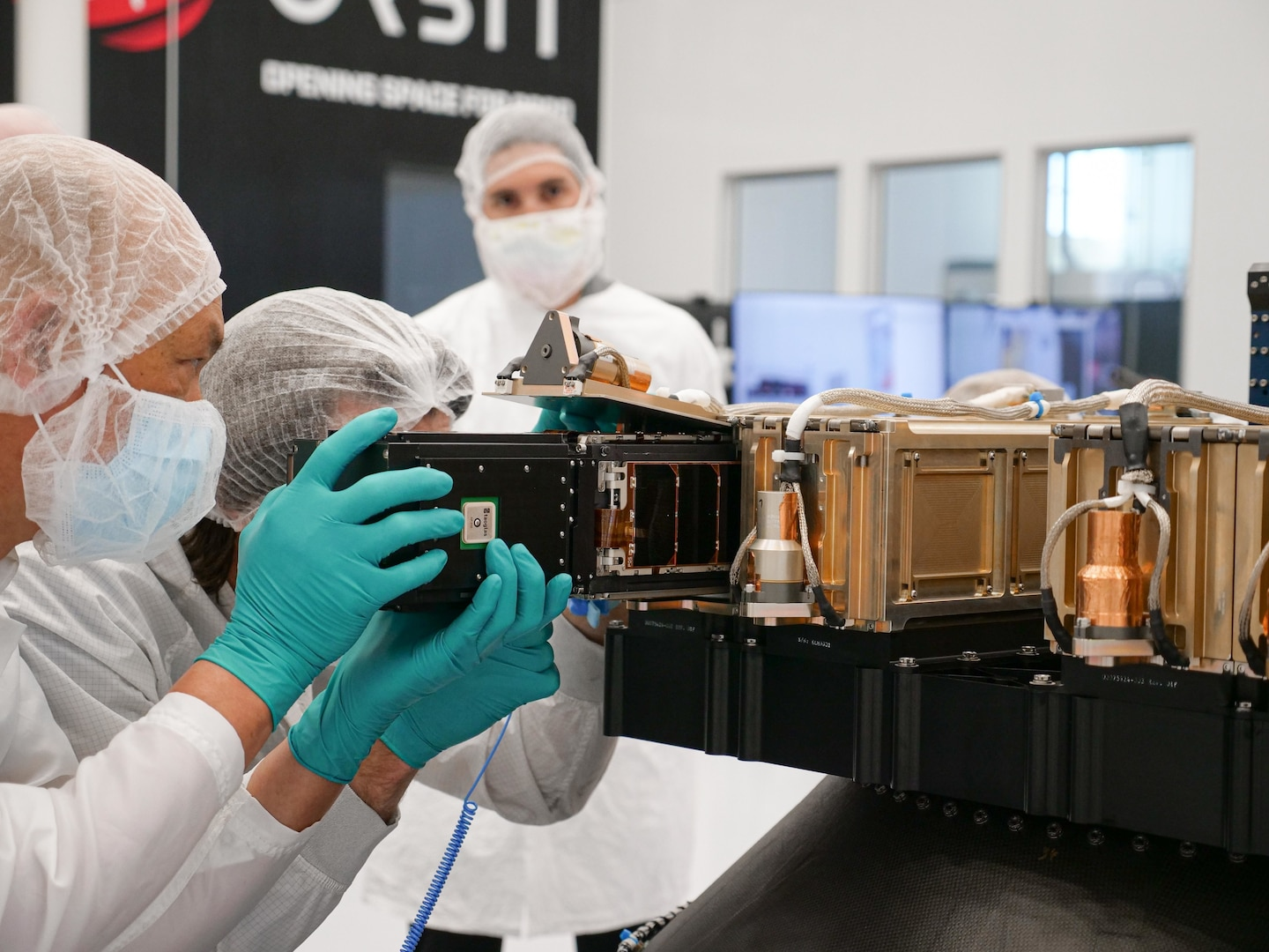 Officials load a satellite.