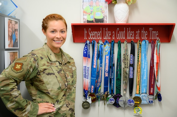 Airman stands in front of a display of her race medals.