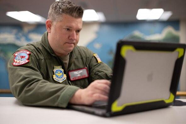 An Airman sitting down at a laptop