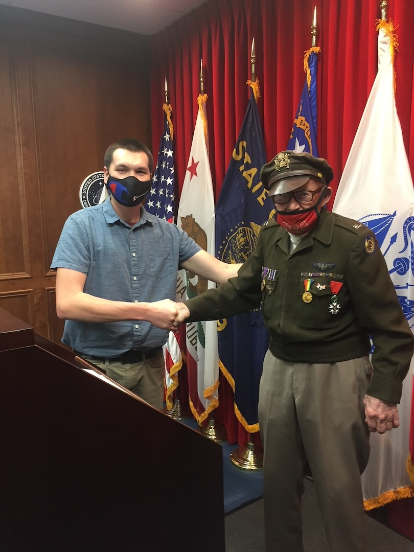 Army applicant Victor Bassett shakes hands with World War II veteran Dennis Thompson during his enlistment ceremony at Sacramento MEPS
