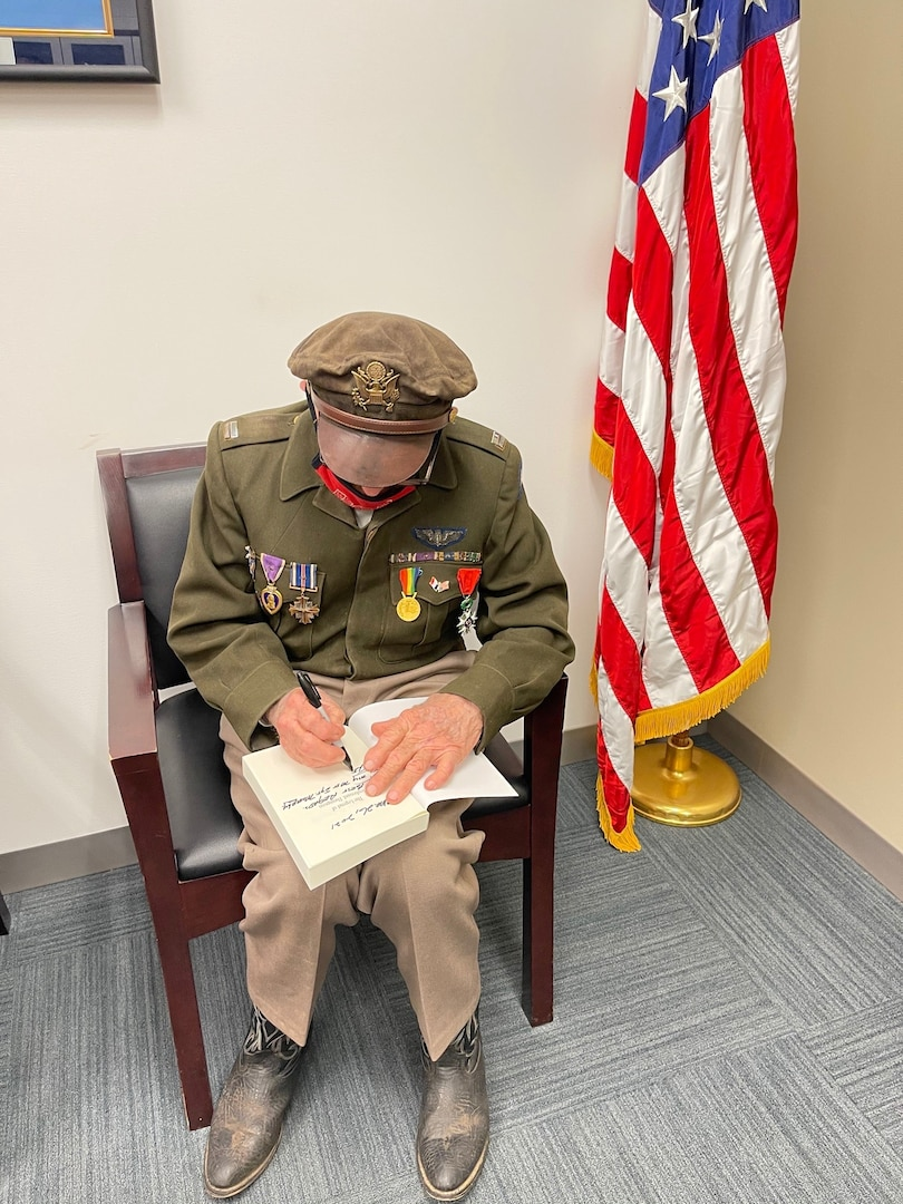 World War II veteran Dennis Thompson signs a copy of his book at Sacramento MEPS
