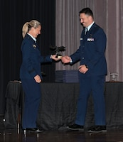 Brigadier General Bobbi Doorenbos (Retired) (Left) hands 2nd Lt. Jack Reis the Order of Daedalians Air Education & Training Command Commander's Trophy July 9, 2021, on Columbus Air Force Base, Miss. The trophy is presented to the students who demonstrate outstanding performance with assigned check rides, daily flying operations, as well as maintains an exceptional commander's ranking and academic score. (U.S. Air Force photo by Airman First Class Jessica Haynie)
