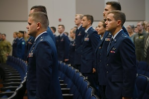 Graduates from Specialized Undergraduate Pilot Training Class 21-12 stand as they await to be presented their awards July 9, 2021, on Columbus Air Force Base, Miss. The graduates completed a 52-week pilot training program including academics, physiological training, and flight training in the T-6A Texan II, T-1A Jayhawk, and T-38C Talon. (U.S. Air Force photo by Airman First Class Jessica Haynie)