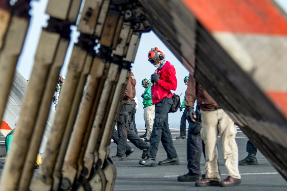 Sailors walk on a ship's deck and look at the ground.