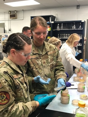 From left, Cadets Julia Gundlach and Olivia Orahood, study agar plates for bacteria colonies inside the Air Force Civil Engineer Center Readiness Laboratory at Tyndall Air Force Base, Fla, June 29, 2021. The cadets were part of the 2021 U.S. Air Force Academy Summer Research Program May 24 – July 2. The cadets worked with experienced Air Force scientists on two project topics – developing a sampling methodology for Per- and Polyfluoroalkyl substances and finding potential solutions to naturally remove and break down the complex, synthetic chemicals in water. The second project explored using bacteria to treat runways and prevent erosion and dust.