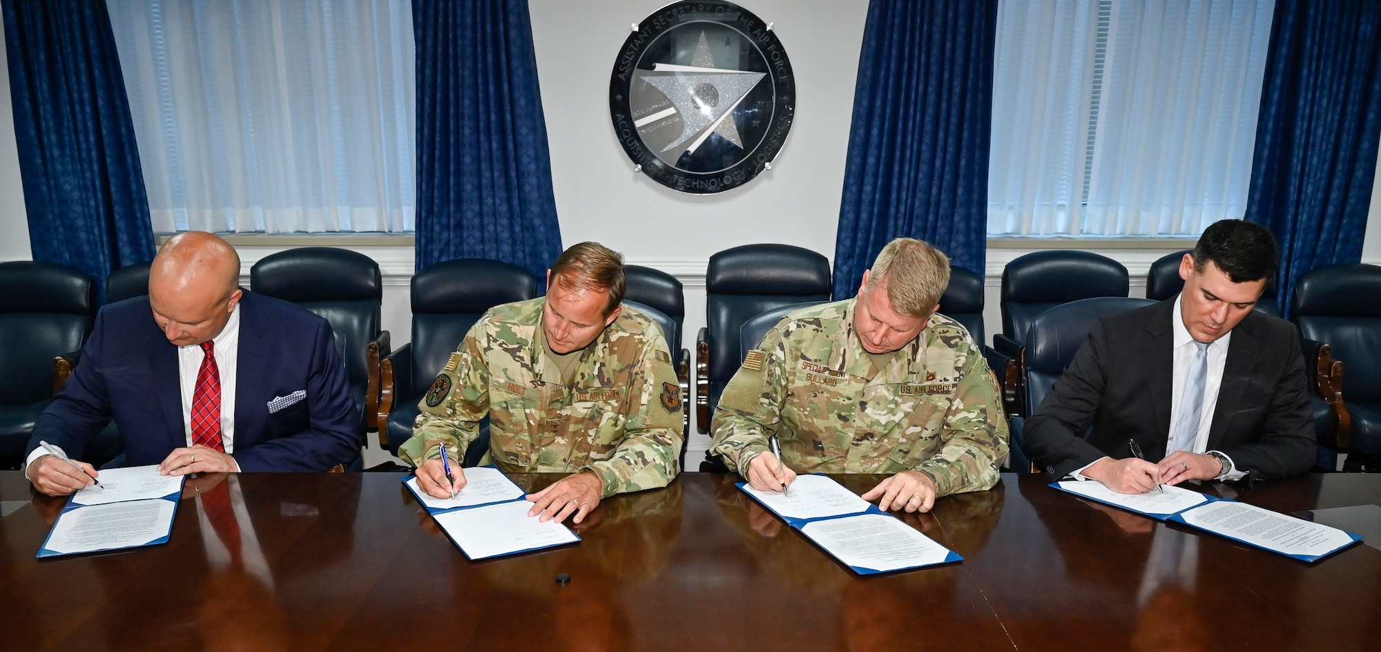 Robert Preston, Judge Advocate General's Corps, Civil Law Domain director; Maj. Gen. Cameron Holt, Office of the Assistant Secretary of the Air Force for Acquisition, Contracting deputy assistant secretary; Brig. Gen. Terry Bullard, Air Force Office of Special Investigations commander; and Derek Santos, Contractor Responsibility and Conflict Resolution deputy general counsel, sign a joint memorandum of understanding at the Pentagon, Arlington, Va., July 8, 2021. The MOU established the Department of the Air Force Acquisition Integrity Working Group.