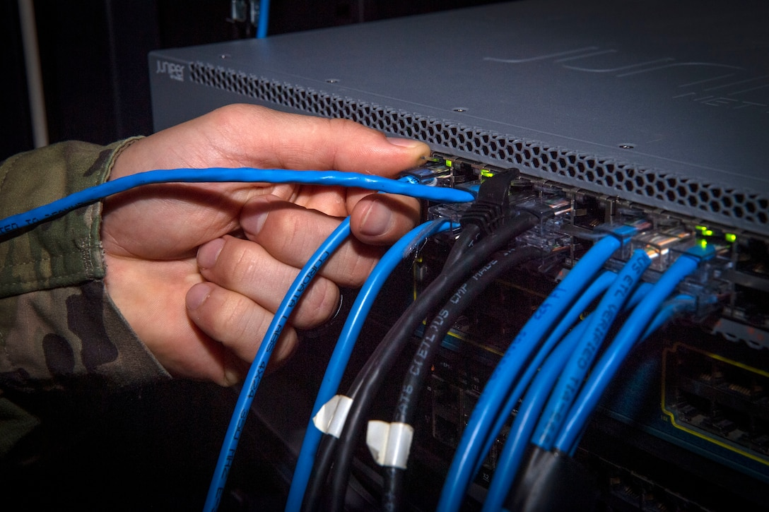 Tech. Sgt. Patrick Gildea, a 6th Communications Squadron (CS) Mission Defense Team supervisor, plugs in a new ethernet cable into a computer server at MacDill Air Force Base, Florida, July 8, 2021.