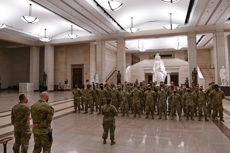 U.S. Army Capt. Tiffany Pelrine, center, 272nd Chemical Company commander with the Massachusetts National Guard, addresses a formation during a combined promotion and award ceremony at the U.S. Capitol building in Washington, D.C., May 21, 2021. The National Guard has been requested to continue supporting federal law enforcement agencies with security, communications, medical evacuation, logistics and safety support to state, district and federal agencies through mid-May. (U.S. Air National Guard photo by Staff Sgt. Hanna Smith)