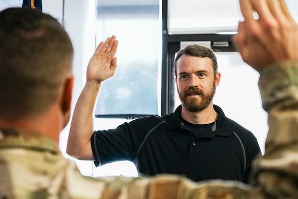 Man holds hand up to take the Oath of Enlistment.