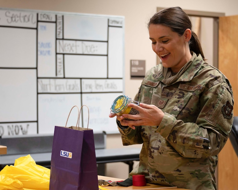 Photo of Airman smiling as she holds a jar of primers.