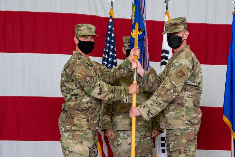 Col. Joshua Wood, 51st Fighter Wing commander, left, receives the 51st Medical Group guidon from Col. Michael Fea, 51st Medical Group outgoing commander, during the change of command ceremony at Osan Air Base, Republic of Korea, July 12, 2021. This act marks the official end of Fea's command of the 51st MDG. (U.S. Air Force photo by Tech. Sgt. Nicholas Alder)