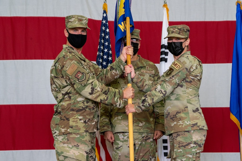 Col. Joshua Wood, 51st Fighter Wing commander, left, presents Col. Jennifer Vecchione, with the 51st Medical Group guidon during the change of command ceremony at Osan Air Base, Republic of Korea, July 12, 2021. This act marks the official beginning of Vecchione's command of the 51st MDG. (U.S. Air Force photo by Tech. Sgt. Nicholas Alder)