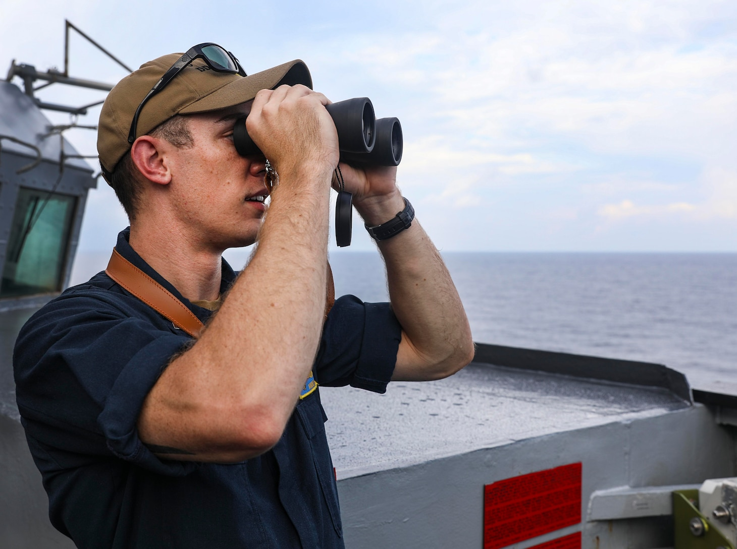 210712-N-FO714-1033 SOUTH CHINA SEA (July 12, 2021) Lt.j.g. Andrew Hayne, from Parker, Colo., uses binoculars to monitor a surface contact from the bridge wing of the Arleigh Burke-class guided-missile destroyer USS Benfold (DDG 65) while conducting routine underway operations. Benfold is forward-deployed to the U.S. 7th Fleet area of operations in support of a free and open Indo-Pacific. (U.S. Navy photo by Mass Communication Specialist 1st Class Deanna C. Gonzales)