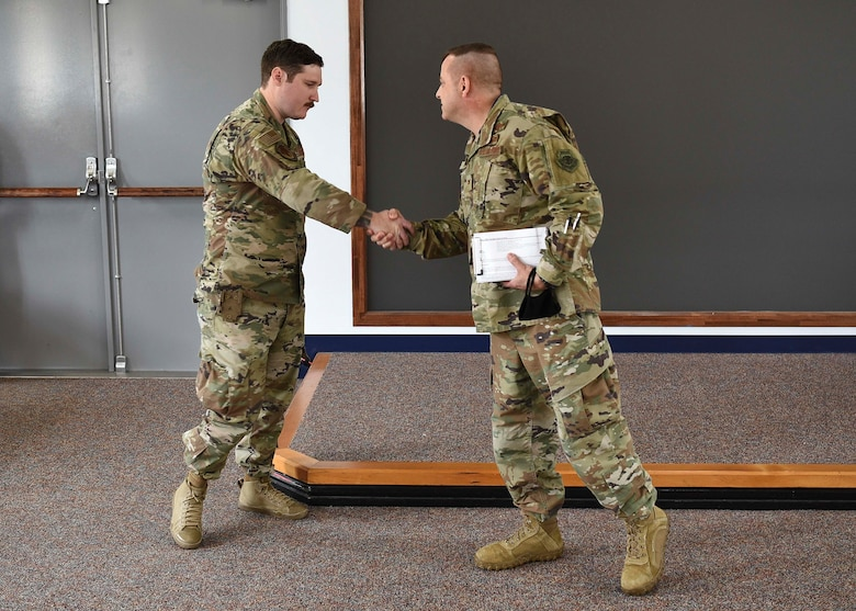 Two military members shake hands. The member on the right coins the one on the left in the hand shake.