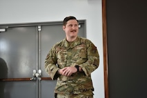 A military member holds his hands as he stands in front of a room.
