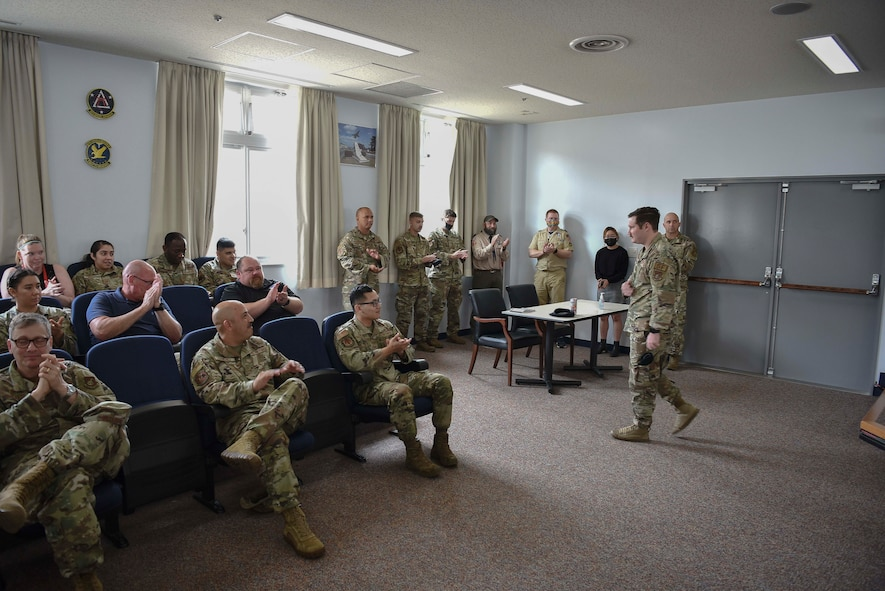 A military member walks across a room as others in the room clap for him.