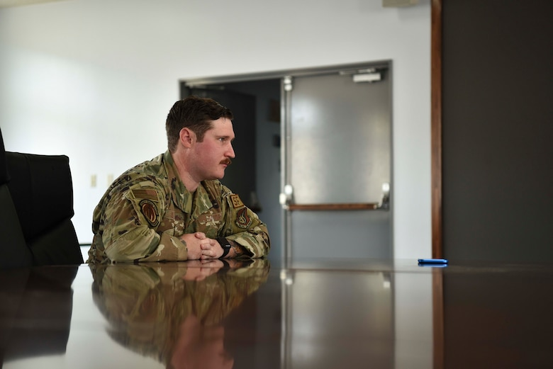 A military member holds his hands over a table looking ahead.
