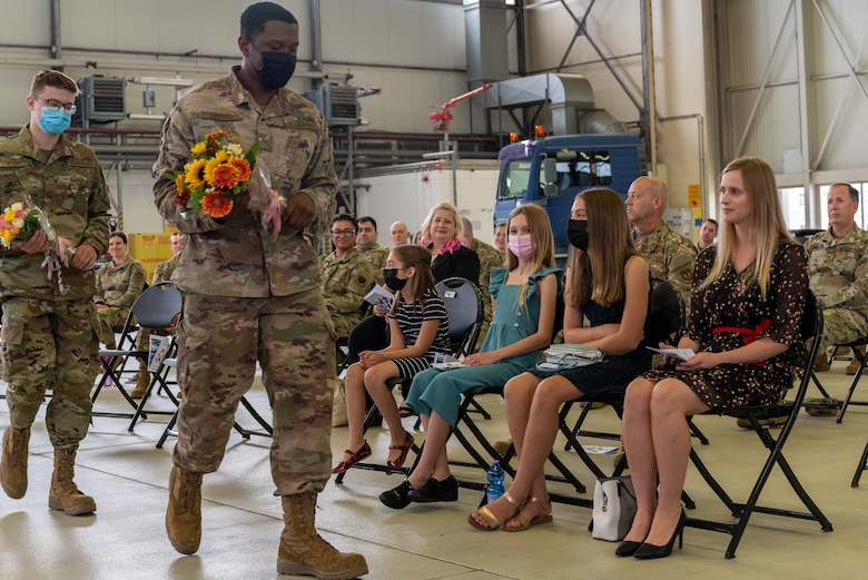 Airmen holding flowers and walking alongside seated crowd.