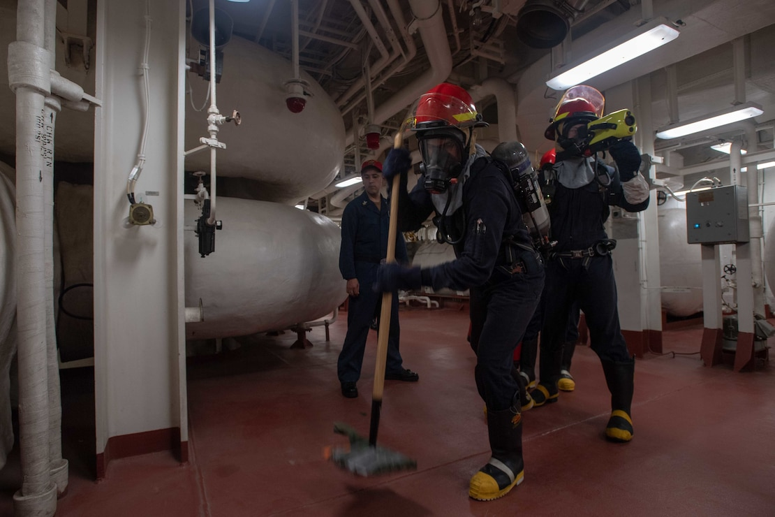 Sailors assigned to forward-deployed amphibious assault ship USS America (LHA 6) practice firefighting techniques during a damage control drill.