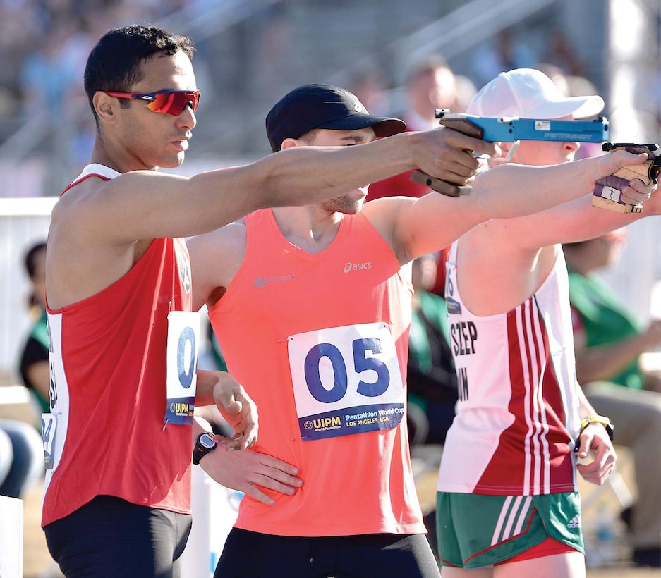Men in athletic gear shoot guns during a pentathlon competition.