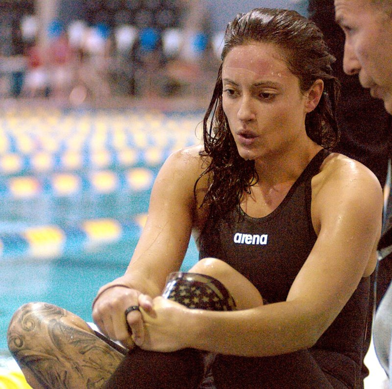 A female swimming athlete sits next to a pool.