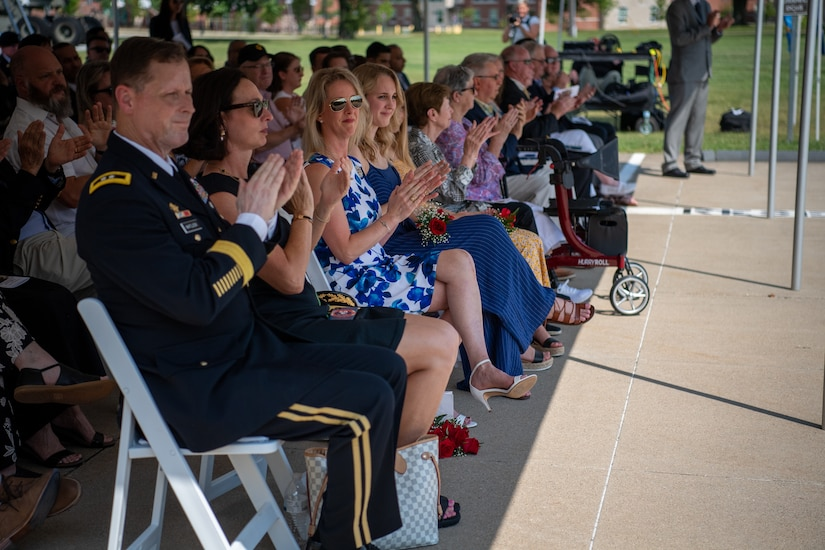 group of people in an audience applaud during a ceremony.