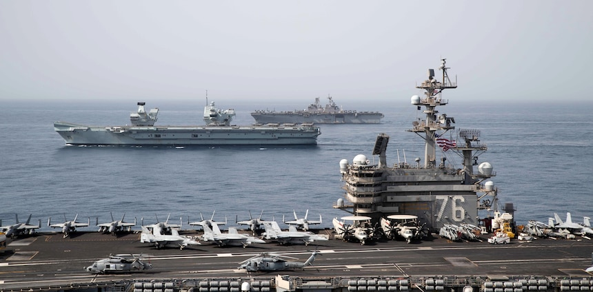 Royal Navy aircraft carrier HMS Queen Elizabeth (R 08), middle, aircraft carrier USS Ronald Reagan (CVN 76) and amphibious assault ship USS Iwo Jima (LHD 7) operate in formation in the Gulf of Aden.