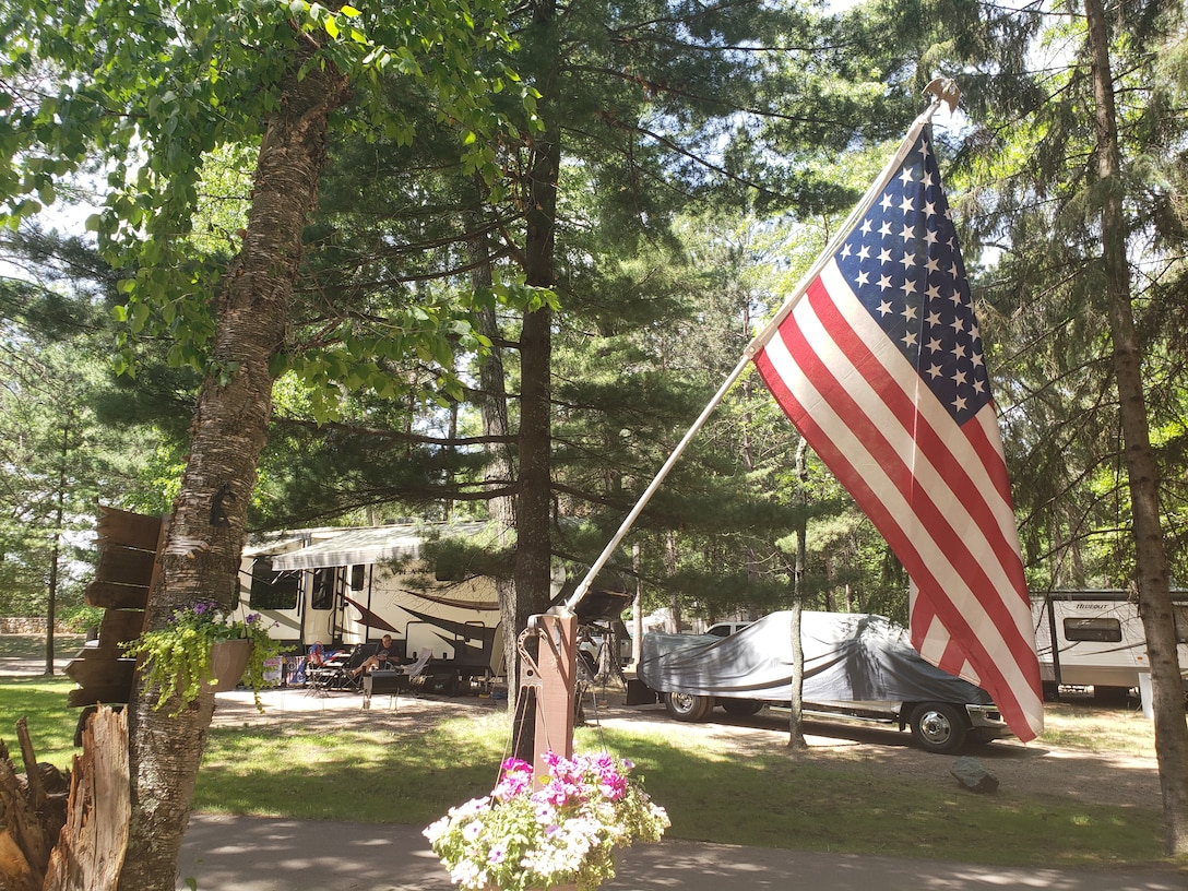 An American flag is displayed at a campsite