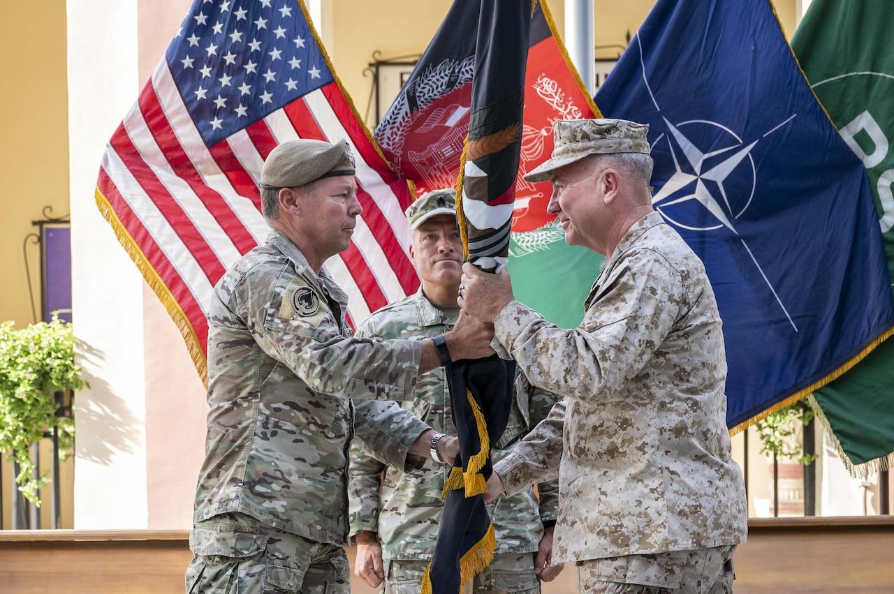 Two men pass a flag.