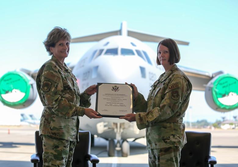 Col Cheryl Knight presents Chief Master Sgt. Saudi McVea with retirement certificate.