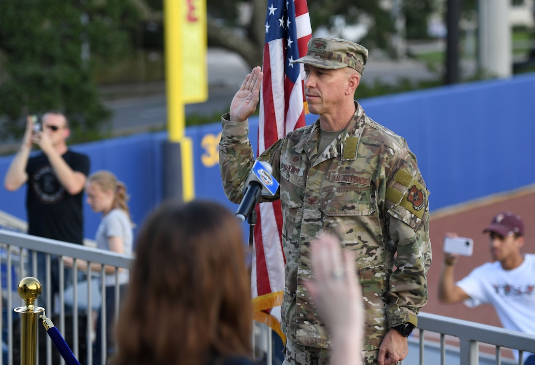 U.S. Air Force Col. William Hunter, 81st Training Wing commander, recites the oath of office to 10 Air Force delayed entry program recruits during the Biloxi Shuckers Minor League Baseball game in Biloxi, Mississippi, July 10, 2021. Hunter also threw the first pitch during pre-game festivities. (U.S. Air Force photo by Kemberly Groue)