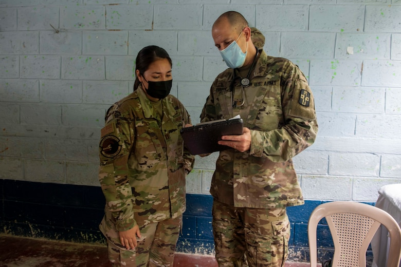 U.S. Air Force Capt. Jennifer Buck, an operations research analyst from the Studies and Analysis Squadron at Joint Base San Antonio-Randolph, Texas, and U.S. Army Maj. Nathan Borden, an emergency medicine M.D., with the 228th Combat Support Hospital of Joint Base San Antonio, Texas, review a patient's chart during Resolute Sentinel 21 in Melchor De Mencos, Guatemala, June 17, 2021. Buck's evaluations help account for proper staffing, planning prescription lists, and how to conduct similar missions in the future.