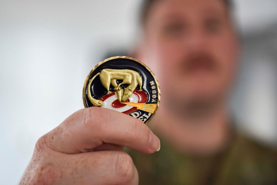 A military member hold up a 35th Fighter Wing coin with the mascot, The Wild weasel, on it holding a bomb to a target with a lightning bolt coming from the side striking it at the same place.