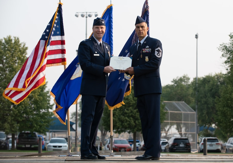 U.S. Air Force Senior Master Sgt. Chad Carrier, 419th Civil Engineer Squadron, receives the Airman's Medal from Col. Matthew Fritz, 419th Fighter Wing commander, during a ceremony at Hill Air Force Base, Utah on July 11, 2021. Carrier displayed exemplary heroism actions when he saved the life of a trapped driver by pulling him from a burning vehicle.