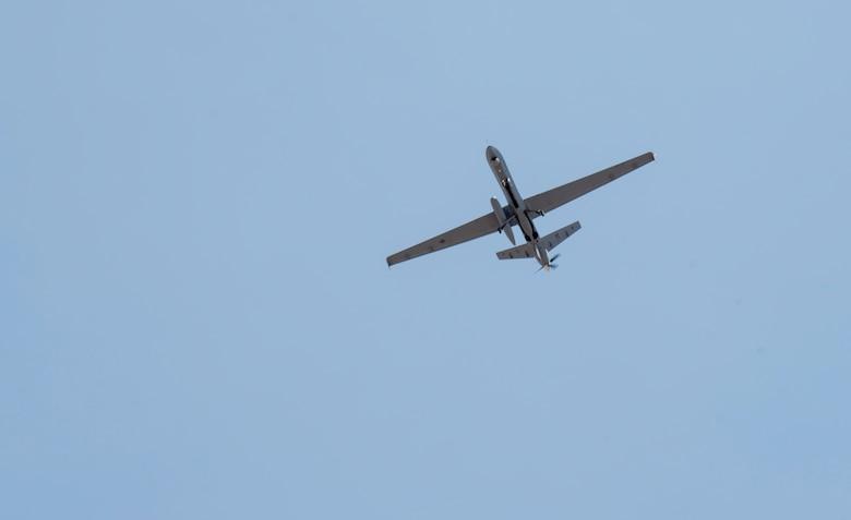An MQ-9 Reaper flies through a clear blue sky over Holloman AFB, New Mexico.