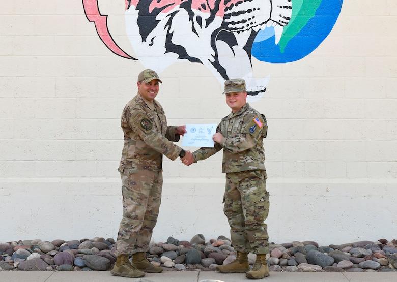 A photo of an airman handing another airman a certificate