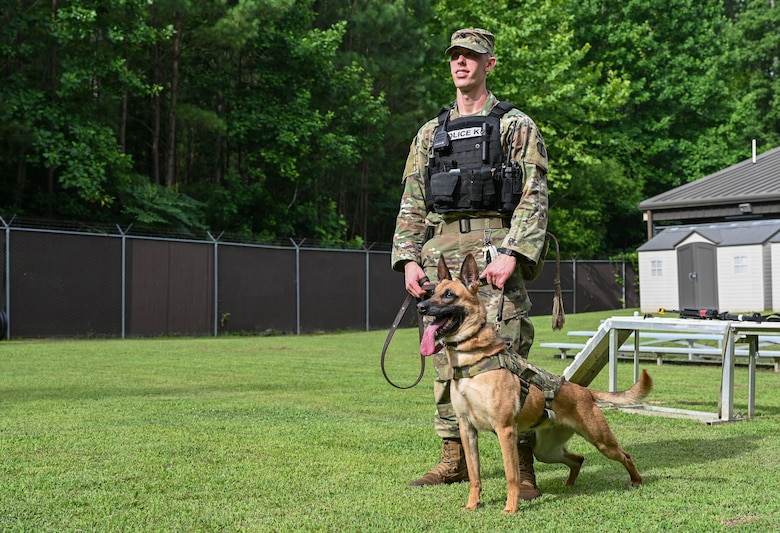 U.S. Army Specialist Taylor Blanton, 3rd Military Police Detachment, Military Working Dog handler, and Military Working Dog Maya, a 5-year-old Belgian Malinois assigned to the 3rd MPD, stand alert at Joint Base Langley-Eustis, Virginia, July 8, 2021. Blanton and Maya have been paired together as a MWD team for the past 8 months. (U.S. Air Force photo by Senior Airman Sarah Dowe)